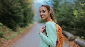 Οδοιπόρος γυναικών με το μικρό σακίδιο πλάτης, που περπατά στο δρόμο στο δάσος φιλμ μικρού μήκους
