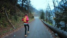 Οδοιπόρος γυναικών με το μικρό σακίδιο πλάτης που τρέχει στον αγροτικό δρόμο στο δάσος φιλμ μικρού μήκους