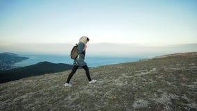 Οδοιπόρος γυναικών που περπατά στην έκταση βουνών που φορά το σακίδιο πλάτης απόθεμα βίντεο