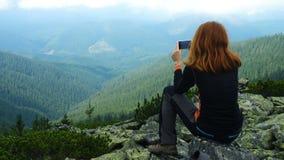 Οδοιπόρος κοριτσιών που παίρνει τη φωτογραφία των λόφων βουνών που στέκονται σε μια κορυφή απόθεμα βίντεο