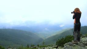 Οδοιπόρος κοριτσιών που παίρνει τη φωτογραφία των λόφων βουνών που στέκονται σε μια κορυφή φιλμ μικρού μήκους