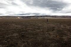 Οδοιπόρος με τα όπλα που αυξάνονται στάση στο ηφαιστειακό τοπίο ενάντια στον ουρανό στοκ εικόνες
