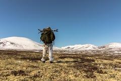 Οδοιπόρος με το μεγάλο σακίδιο πλάτης που περπατά στα χειμερινά βουνά σε Dovre, Νορβηγία Αριστερή πλευρά Στοκ Εικόνες