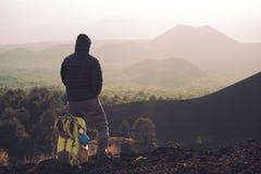 Οδοιπόρος με το σακίδιο πλάτης που απολαμβάνει το ηλιοβασίλεμα στον παλαιό ηφαιστειακό κώνο Etna στο πάρκο στοκ φωτογραφία