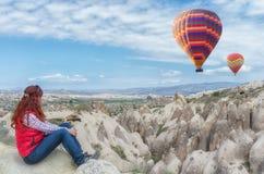 οδοιπόρος που απολαμβάνει τα ζωηρόχρωμα μπαλόνια ζεστού αέρα σε Cappadocia, Τουρκία Στοκ φωτογραφία με δικαίωμα ελεύθερης χρήσης