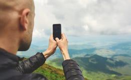 Οδοιπόρος που απολαμβάνει τη θέα και που παίρνει τις φωτογραφίες τηλεφωνικώς στην κορυφογραμμή βουνών r στοκ φωτογραφίες