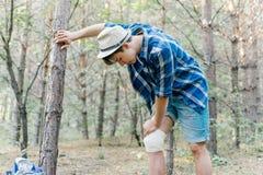 Οδοιπόρος που εφαρμόζει έναν επίδεσμο σε ένα δάσος κατά τη διάρκεια του πεζοπορώ στοκ εικόνες