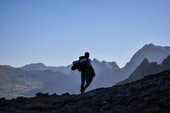 Οδοιπόρος που περπατά στην κορυφογραμμή ενός βουνού στοκ εικόνες
