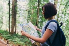 Οδοιπόρος που χρησιμοποιεί έναν χάρτη για να εντοπίσει τον προορισμό στο δάσος στοκ φωτογραφία