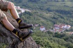 Οδοιπόρος στις μπότες που χαλαρώνουν στο βράχο στοκ φωτογραφία με δικαίωμα ελεύθερης χρήσης