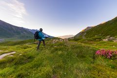 Οδοιπόρος backpacker με το χάρτη οδοιπορίας στην ανατολή στις ιταλικές γαλλικές Άλπεις Στοκ Εικόνες