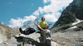Οδοιπόρων ατόμων τουριστών στα βουνά που κάθονται σε μια πέτρα, που χαλαρώνουν και που κατευνάζουν στις άγρια περιοχές στοκ εικόνα