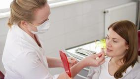 Οδοντίατρος γυναικών που μιλά με το θηλυκό ασθενή στην κλινική Θηλυκός επαγγελματικός γιατρός στην εργασία Οδοντικός έλεγχος επάν φιλμ μικρού μήκους