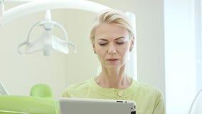 Οδοντίατρος γυναικών που χρησιμοποιεί τον υπολογιστή ταμπλετών Οδοντικό επαγγελματικό χρησιμοποιώντας PC ταμπλετών απόθεμα βίντεο