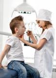 Οδοντίατρος και ασθενής παιχνιδιού κοριτσιών και αγοριών παιδιών στο οδοντικό γραφείο Το Stomatologist ελέγχει τα υπομονετικά δόν στοκ εικόνα με δικαίωμα ελεύθερης χρήσης