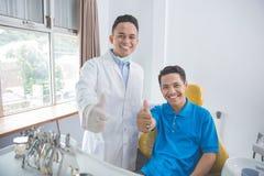 Οδοντίατρος και ασθενής που δίνουν τους αντίχειρες επάνω στο γραφείο οδοντιάτρων Στοκ Εικόνες