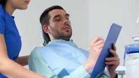 Οδοντίατρος και ασθενής που συζητούν την οδοντική θεραπεία απόθεμα βίντεο