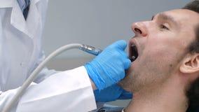 Οδοντίατρος με τη μηχανή τρυπανιών που θεραπεύει τον πελάτη απόθεμα βίντεο