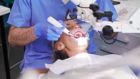 Οδοντίατρος με τον οδοντικό εξοπλισμό που κάνει την εργασία του στην κλινική του οδοντιάτρου απόθεμα βίντεο