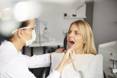 Οδοντίατρος με το οδοντικό τρυπάνι που καθαρίζει τα δόντια του κακού ασθενή στοκ φωτογραφία με δικαίωμα ελεύθερης χρήσης
