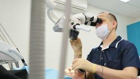Οδοντίατρος με το προσοφθάλμιο μικροσκοπίων Ο οδοντίατρος θεραπεύει τον ασθενή στο σύγχρονο οδοντικό γραφείο Αρσενικός οδοντίατρο απόθεμα βίντεο