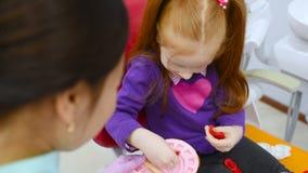 Οδοντίατρος παιδιών και ένα υπομονετικός-μικρό κορίτσι με το κόκκινο παιχνίδι τρίχας με το παιχνίδι οδοντικό όργανο-που φορμάρει  φιλμ μικρού μήκους