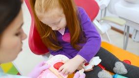 Οδοντίατρος παιδιών και ένα υπομονετικός-μικρό κορίτσι με το κόκκινο παιχνίδι τρίχας με το παιχνίδι οδοντικό όργανο-που φορμάρει  απόθεμα βίντεο