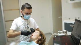 Οδοντίατρος που ανιχνεύει τα δόντια του ασθενή με έναν ανιχνευτή δ φιλμ μικρού μήκους