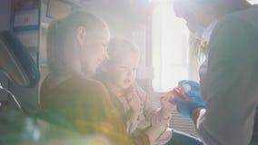 Οδοντίατρος που εξετάζει και που συμβουλεύεται τη συνεδρίαση κορών για τα γόνατα μητέρων της στοκ εικόνες με δικαίωμα ελεύθερης χρήσης