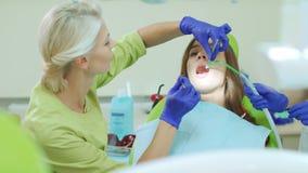 Οδοντίατρος που εξετάζει τα υπομονετικά δόντια με τα οδοντικά εργαλεία ασθενής γιατρών απόθεμα βίντεο