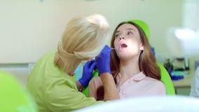 Οδοντίατρος που εξετάζει τα υπομονετικά δόντια με το στοματικό καθρέφτη Stomatologist και ασθενής απόθεμα βίντεο