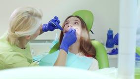 Οδοντίατρος που εξετάζει τα υπομονετικά δόντια με το στοματικό καθρέφτη και τον οδοντικό έλεγχο φιλμ μικρού μήκους