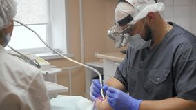 Οδοντίατρος που εξετάζει το τα υπομονετικά δόντια ` s φιλμ μικρού μήκους