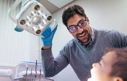 Οδοντίατρος που επιθεωρεί τη στοματική κοιλότητα του μικρού παιδιού στοκ εικόνες
