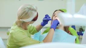 Οδοντίατρος που εργάζεται με τον οδοντικό λαμπτήρα πολυμερισμού στη στοματική κοιλότητα απόθεμα βίντεο