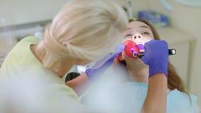 Οδοντίατρος που εργάζεται με τον οδοντικό λαμπτήρα πολυμερισμού στη στοματική κοιλότητα Επεξεργασία δοντιών απόθεμα βίντεο