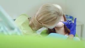 Οδοντίατρος που κάνει την αναισθησία της νέας γυναίκας Θηλυκός οδοντίατρος που χρησιμοποιεί το στοματικό καθρέφτη απόθεμα βίντεο