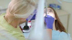 Οδοντίατρος που κάνει τον επαγγελματικό καθαρισμό δοντιών του θηλυκού ασθενή στην οδοντική κλινική απόθεμα βίντεο