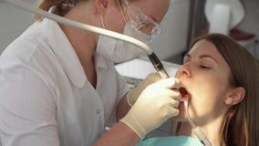 Οδοντίατρος που μεταχειρίζεται τα δόντια στον ασθενή γυναικών στην κλινική Θηλυκός επαγγελματικός γιατρός στην εργασία εξέταση οδ φιλμ μικρού μήκους