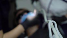 Οδοντίατρος που μεταχειρίζεται τα δόντια στον ασθενή γυναικών στην κλινική Θηλυκό επαγγελματικό stomatologist γιατρών στην εργασί απόθεμα βίντεο