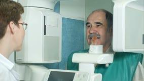 Οδοντίατρος που μιλά σε έναν ανώτερο ασθενή πριν από την εξέταση με τη χρησιμοποίηση του πανοραμικού και cephalometric ανιχνευτή  φιλμ μικρού μήκους