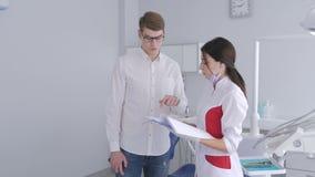 Οδοντίατρος που μιλά σε έναν ασθενή στο οδοντικό γραφείο φιλμ μικρού μήκους