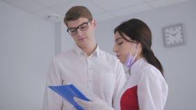 Οδοντίατρος που μιλά σε έναν ασθενή στο οδοντικό γραφείο απόθεμα βίντεο