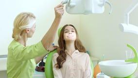 Οδοντίατρος που ρυθμίζει τον οδοντικό λαμπτήρα στον εργασιακό χώρο οδοντιάτρων Επαγγελματίας στοματολογίας απόθεμα βίντεο