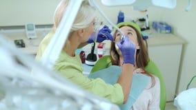 Οδοντίατρος που τρυπά το άρρωστο δόντι του ασθενή γυναικών με τρυπάνι Stomatologist που χρησιμοποιεί το οδοντικό τρυπάνι απόθεμα βίντεο