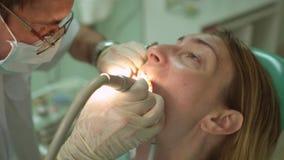 Οδοντίατρος που χρησιμοποιεί τον ειδικό οδοντικό εξοπλισμό στην κλινική με όμορφο υπομονετικό στενό επάνω γυναικών φιλμ μικρού μήκους