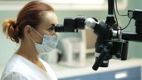 Οδοντίατρος που χρησιμοποιεί το οδοντικό μικροσκόπιο στην οδοντιατρική απόθεμα βίντεο