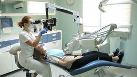 Οδοντίατρος που χρησιμοποιεί το οδοντικό μικροσκόπιο στην οδοντιατρική για τη λειτουργία ενός ασθενή γυναικών φιλμ μικρού μήκους