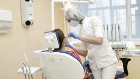 Οδοντίατρος στην εργασία Επαγγελματικό stomatologist γιατρών κατά τη διάρκεια των δοντιών απολαύσεων απόθεμα βίντεο