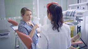 Οδοντίατρος στο οδοντικό γραφείο που η εργασία της σε έναν ασθενή απόθεμα βίντεο